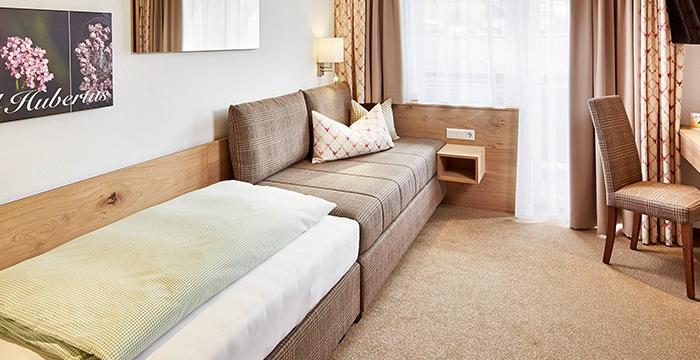 Einzelbett mit Sitzcouch gegenüber von Wandfernseher, Schreibtisch, Stuhl und Kasten