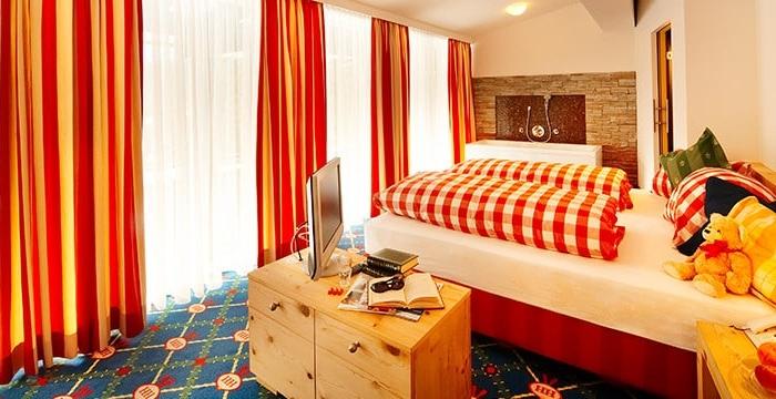 Doppelbett mit Nachtisch und kleiner Kommode auf der Fernseher steht