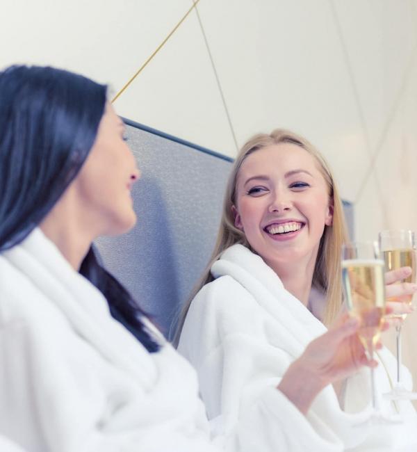 2 Freundinnen tragen Bademäntel und prosten sich gegenseitig mit Sektgläsern zu