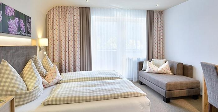 Doppelbett steht an Wand gegenüber von Schlafsofa, Schreibtisch und Stuhl über dem Wandfernseher hängt