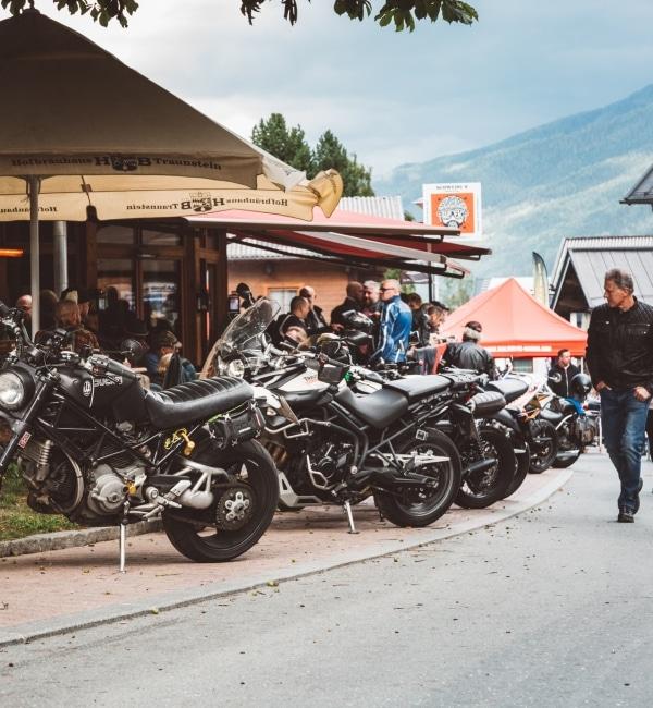 Motorräder stehen neben Lokal und Passanten gaffen