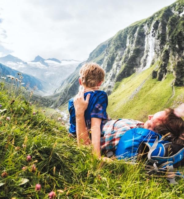Vater liegt im Gras umarmt Sohn der daneben sitzt