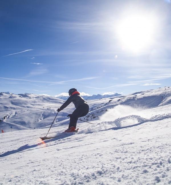 Skifahrerin fährt bei strahlendem Sonnenschein Piste hinunter