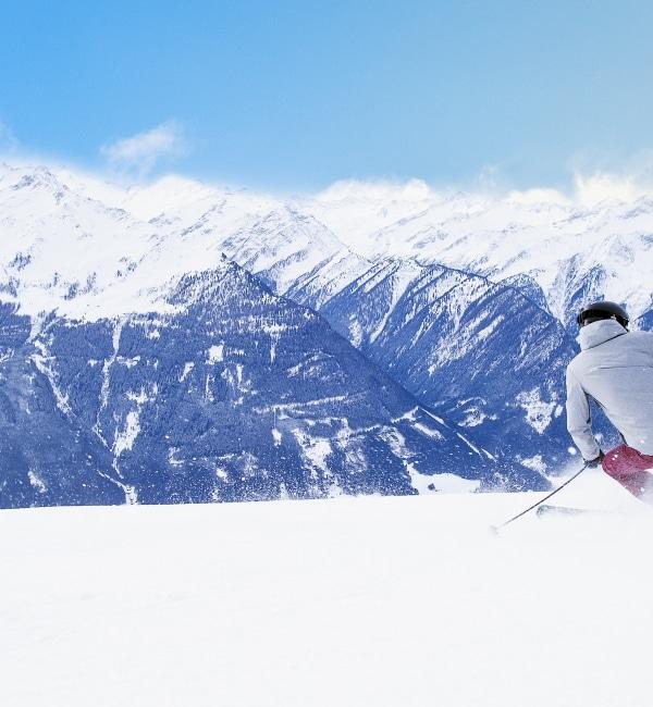 Skifahrer wedelt Piste der Wildkogel Arena hinunter